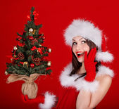 Girl in santa hat holding christmas tree. — Stock Photo