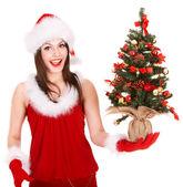 Girl in santa hat holding christmas tree. — Stock fotografie