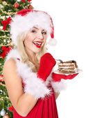 Christmas girl in santa hat and cake on plate. — Stock Photo