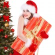 Girl in santa hat holding gift box by christmas tree.. — Stock Photo #7893548