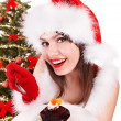Christmas girl in Santa hat eating cake. — Stock Photo #7893555