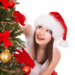 Girl in santa hat by christmas tree. - Stock Photo