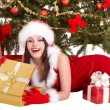 Christmas girl in santa hat, fir tree, gift box group. - Stock Photo