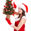 Girl in santa hat holding christmas tree. - Stock Photo