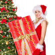 Girl in santa hat holding  gift box by christmas tree.. — Stock Photo