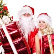 Santa claus and girl holding gift box by christmas tree.. — Stock Photo