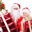 Santa claus and girl holding gift box by christmas tree.. — Stock Photo #7894153