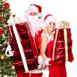 Santa claus and girl holding gift box by christmas tree.. — Стоковое фото #7894154