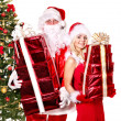 Santa claus and girl holding gift box by christmas tree.. — Photo #7894154