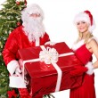 Santa claus and girl holding gift box by christmas tree.. — Stock Photo #7894178