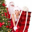 Santa claus and girl holding gift box by christmas tree.. — Stock Photo #7894179