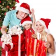 Happy family in santa hat holding gift box. — Stock Photo
