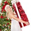 Christmas girl in santa hat giving red gift box. — Stock Photo