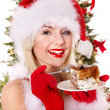 Christmas girl in Santa hat and cake on plate. - Stock Photo