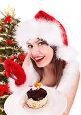 Christmas girl in Santa hat eating cake. — Stock Photo
