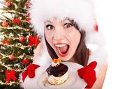 圣诞老人帽的女孩吃蛋糕的圣诞树. — 图库照片