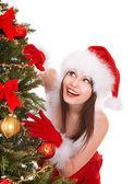 Meisje in kerstman hoed door kerstboom. — Stockfoto