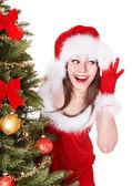 Meisje in kerstman hoed luisteren in de buurt van de kerstboom. — Stockfoto