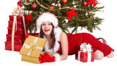 Christmas girl in santa hat, fir tree, gift box group. — Stock Photo
