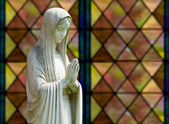 Isolated statue of Mary against window — Stock Photo