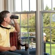 Man watching bird on feeder — Stock Photo