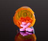 Fialová pilulky z oranžové lék láhev — Stock fotografie