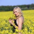 Beautiful young blonde woman in a field of wildflowers. — Stock Photo