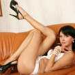 Glamour model poses on the leather sofa. — Stock Photo