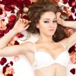 Young  woman in rose petals. — Stock Photo