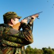 Hunter shooting with rifle gun - Stock Photo