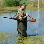 Hunter with rifle gun in bog — Stock Photo
