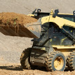 Skid steer loader at earth moving works - Stock Photo