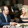 Man and girl with wine at cafe on a date — Stockfoto