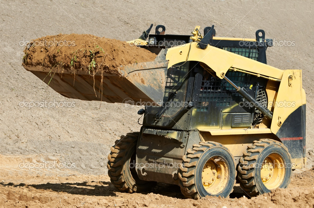 Skid steer loader moving sand soil at construction area outdoors — Stock Photo #6768680