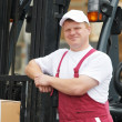 Стоковое фото: Warehouse worker in front of forklift