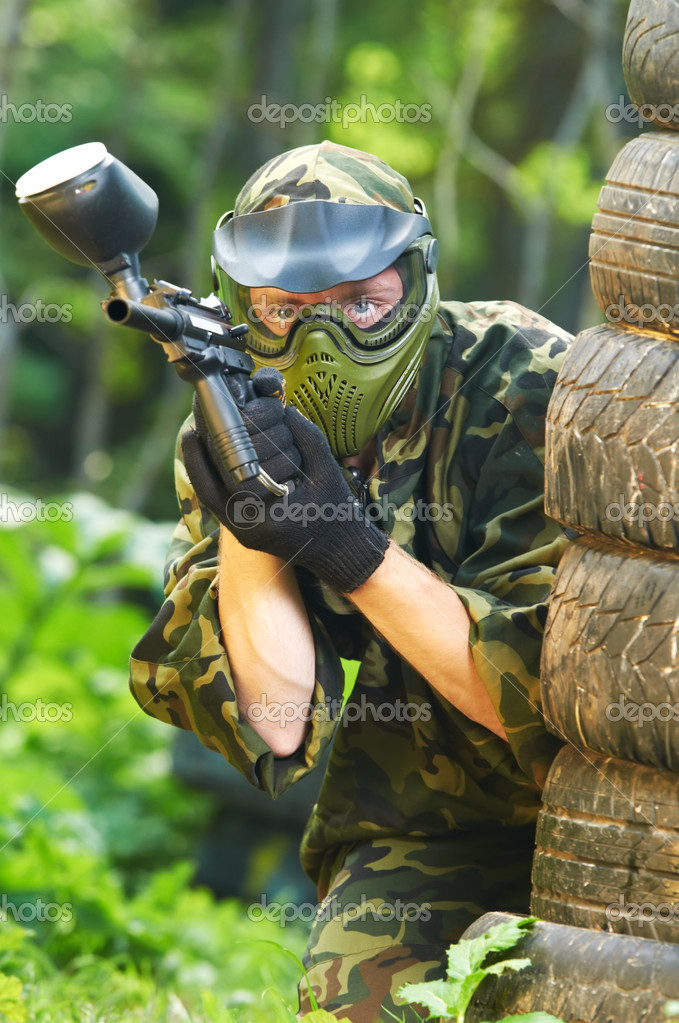 Paintball sport player in protective uniform and mask aiming and shooting with gun outdoors  Stock Photo #6937661
