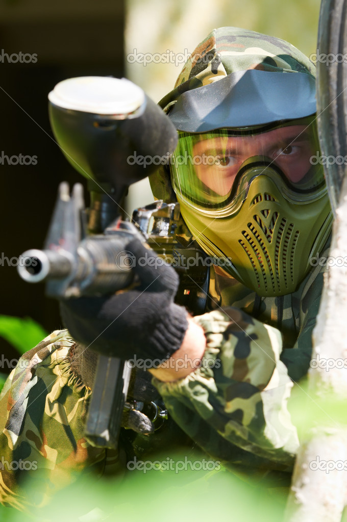 Paintball sport player in protective uniform and mask aiming and shooting with gun outdoors — Stock Photo #6937701