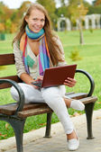 One smiling young girl with laptop outdoors — Stock Photo