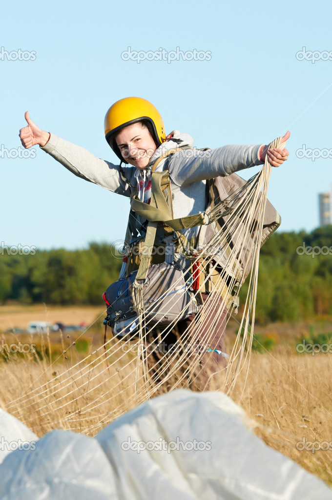 Single Happy parachute jumper after landing at field and blue sky background — Stock Photo #6961278