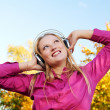Woman with headphones at autumn outdoors — Stock Photo