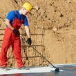 Builder worker at roof insulation work - Stock Photo