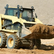Stock Photo: Skid steer loader at earth moving works
