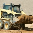 Skid steer loader at earth moving works — Stock Photo #7142157