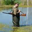 Hunter with rifle gun in bog — Stock Photo