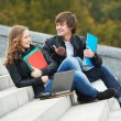 Two smiling young students outdoors — Stock Photo