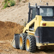 Skid steer loader at earth moving works — Stock Photo #7148130