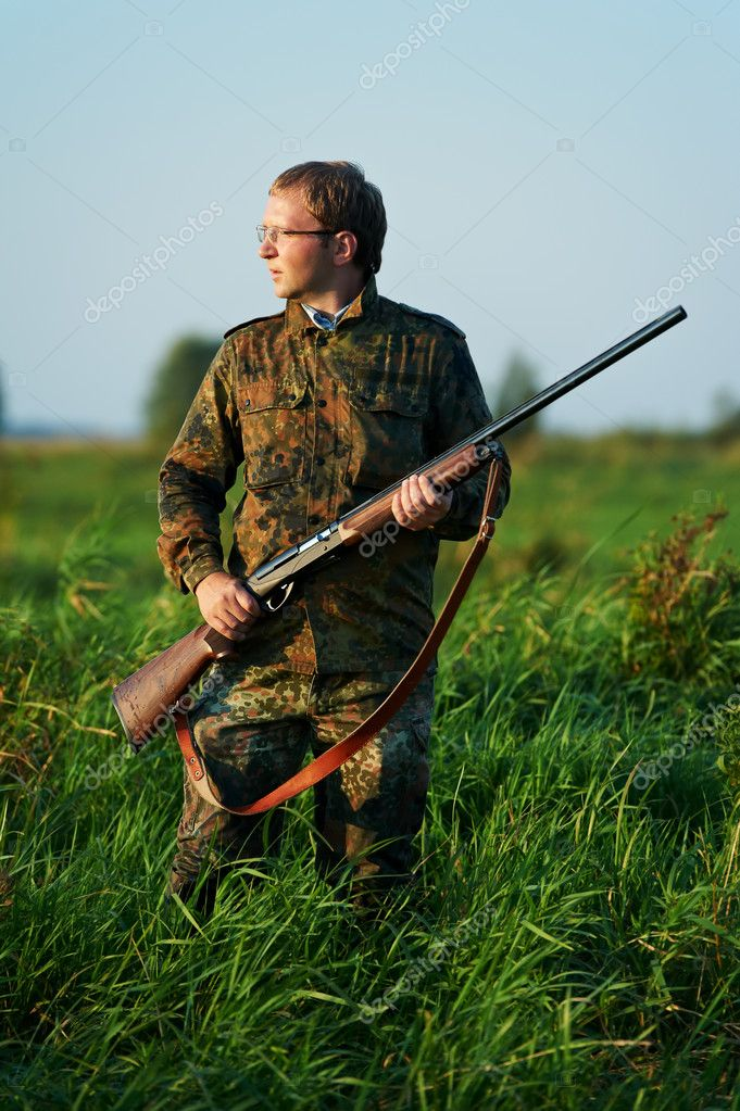 Male hunter in camouflage clothes ready to hunt at lake bank with hunting rifle  Stock Photo #7142263