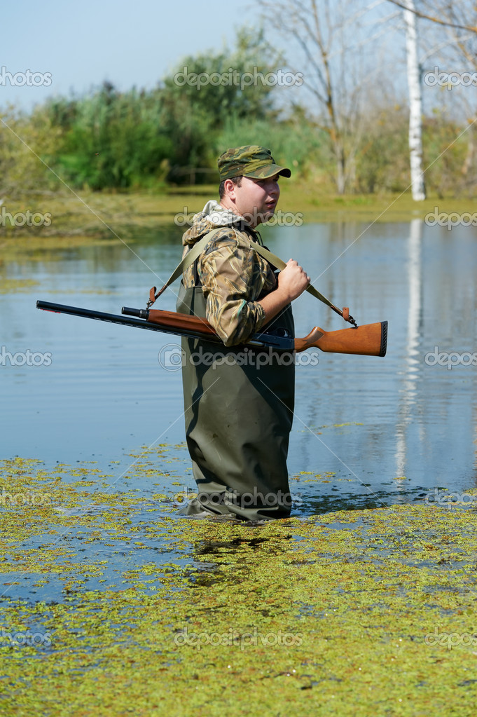 Male hunter in camouflage clothes standing at water bog with hunting rifle during a hunt — Stock Photo #7142344