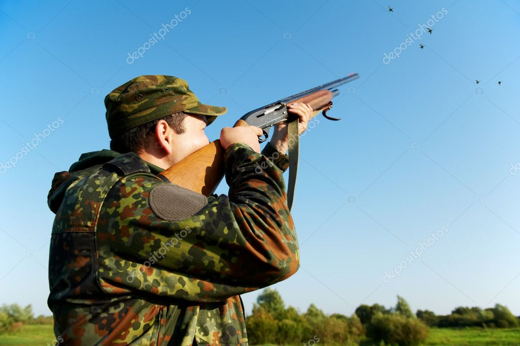 Male hunter in camouflage clothes on the field aiming and shooting with hunting rifle to gamebird during a hunt — Stock Photo #7142351