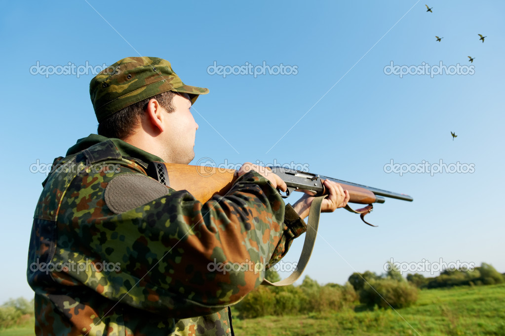 Male hunter in camouflage clothes on the field aiming and shooting with hunting rifle to gamebird during a hunt — Stock Photo #7142358